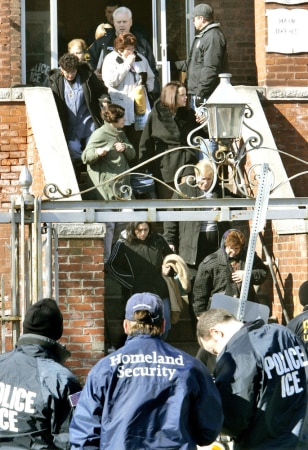 Image: Employees are escorted out after an early morning raid by federal immigration officials at the Michael Bianco Inc. textile plant in New Bedford, Mass.
