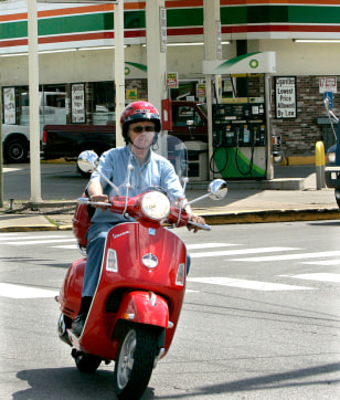 Image: A man rides his scooter past a gas station