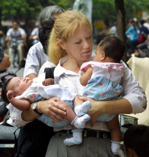 Image: American woman holds two Vietnamese girls