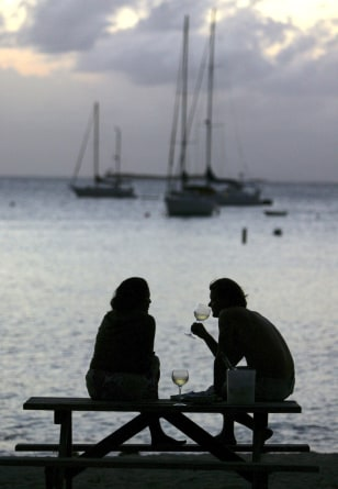 Image: couple drinks white wine at the end of the day on a beach near Charlotte Amalie, St. Thomas, U.S. Virgin Islands