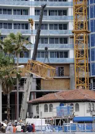 Image: Construction workers look on as a section of a crane is lifted from a house and set on the ground