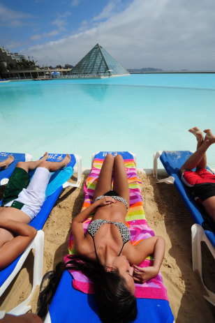 Image: Tourists sunbathe in the world's largest swimming pool at a seaside resort in Algarrobo, 95 km west from Santiago