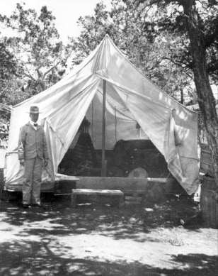 Image:John George Verkamp stands by his tent .