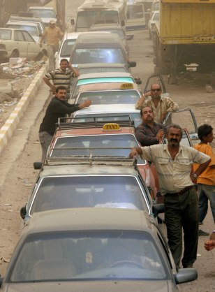 Image: Motorists wait in line at a gas station in Baghdad