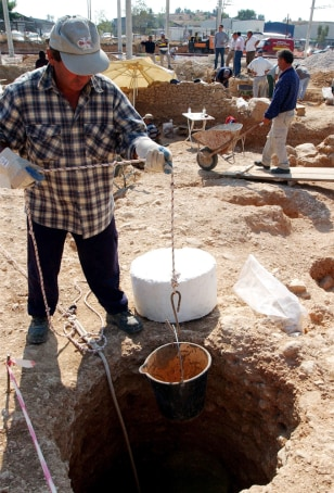 Worker lowers bucket into hole at archaeological site