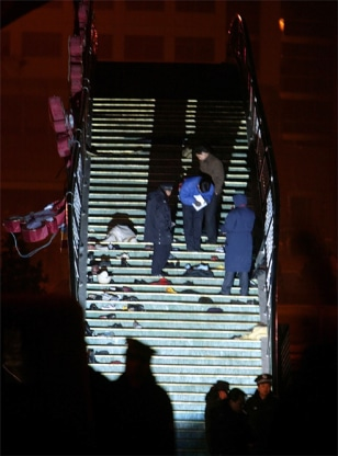 CHINESE POLICE CHECK BELONGINGS OF VICTIMS LEFT ON A FOOTBRIDGE AFTER A STAMPEDE AT A GALA CELEBRATING THE LANTERN FESTIVAL NEAR BEIJING