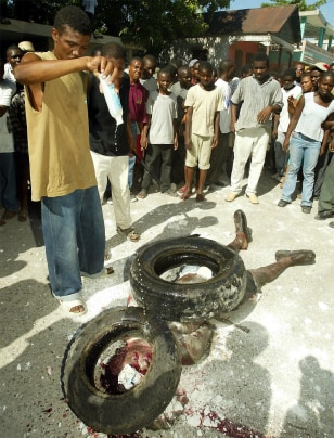 MAN POURS GASOLINE ON SUSPECTED HAITIAN ASSASSIN