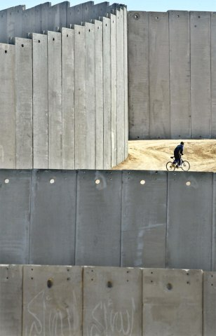 AN PALESTINIAN BOY RIDES ON A BICYCLE NEAR A PART OF ISRAELS CONTROVERSIAL SECURITY BARRIER IN EAST JERUSALEM