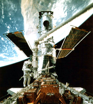 Astronaut works on Hubble