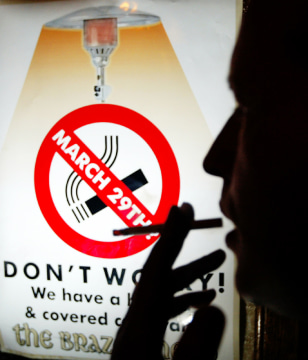 Image: Man smokes cigarette in front of Irish smoking ban sign.
