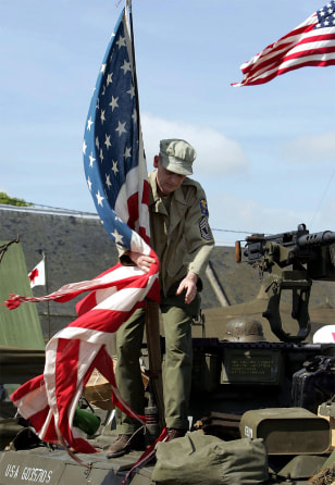 A FRENCH WW II HISTORY BUFF WRAPS THE US FLAG AROUND ITS MAST ON A VINTAGE TANK AT OMAHA BEACH