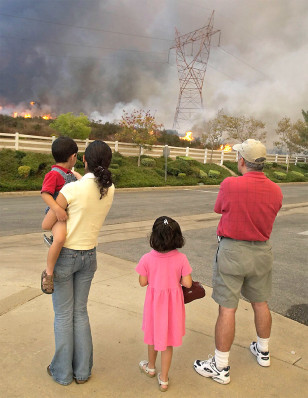 FAMILY WATCHES FLAMES APPROACH THEIR HOSUING COMPLEX AT RANCHO CUCAMONGA