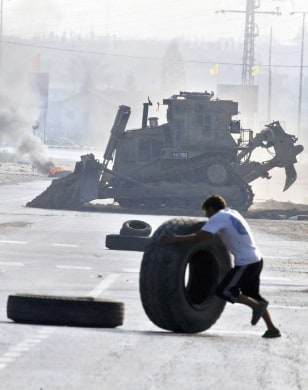 Image: Palestinian rolls a tire to erect a barricade.