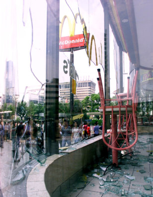 PASSERS-BY WALK PAST SMASHED WINDOWS OF A MCDONALDS RESTAURANT IN JAKARTA'S CHINATOWN