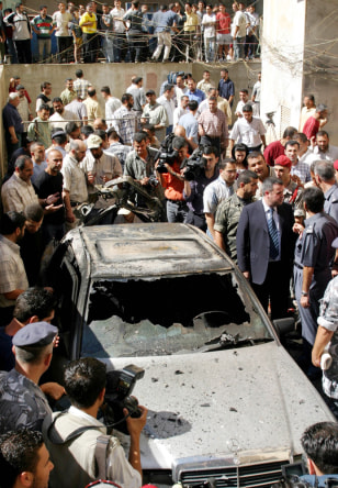 Image: Lebanese security surround destroyed car.
