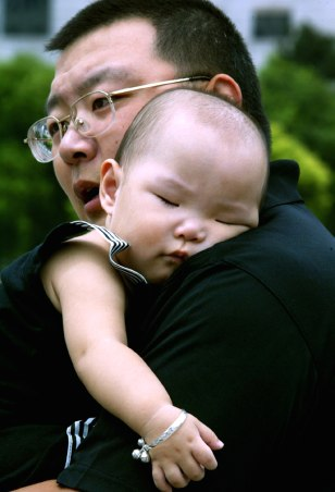 A Chinese father carries his sleeping child at a park in Shanghai