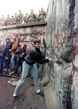 File photo shows a demonstrator breaking the Berlin Wall