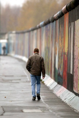An unidentified man walks past remains of the Berlin Wall