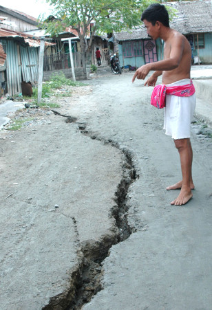 A man inspects a crack after an earthquake