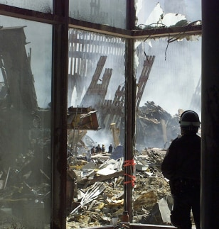 Image: New York police officer looks at wreckage of World Trade Center.