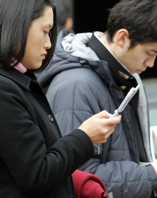 Woman reads a mobile phone screen in Tokyo
