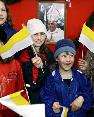 Children wave flags in front of a pictur