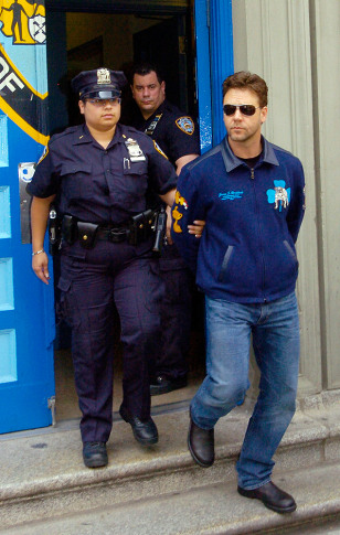 Russell Crowe is walked out of police station by police after arrest in New York City