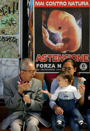 Passengers wait at a bus station Friday in front of a poster calling on Italians to abstain from voting Sunday.