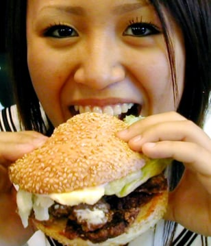 Image: Japanese woman eats whale burger.