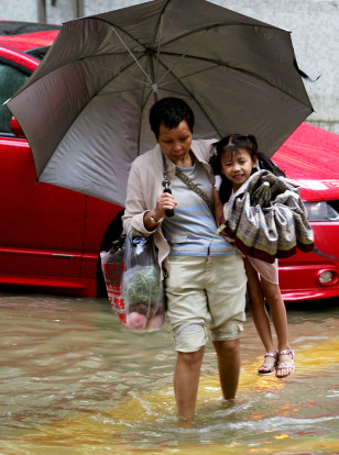 A woman carries a girl as she wades through flood waters, Hong Kong