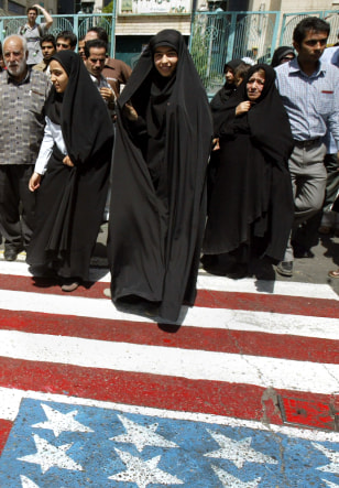 Iranian women walk on a US flag painted