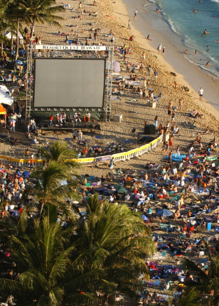 crowd gathers in front of screen at Wakiki Beach