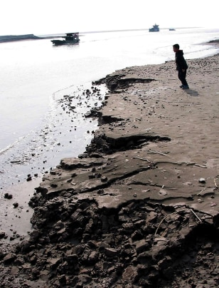 A boy plays by the eroding banks of the Yangtze