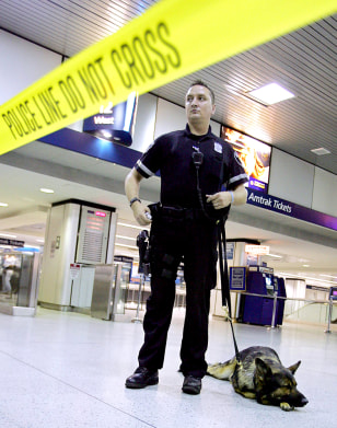 A police officer and a dog stand behind police lines in Penn Station in New York City