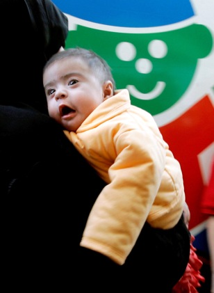 File photo of Iraqi baby Noor being carried to waiting ambulance after arriving in Atlanta