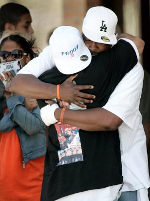 Image: Mourners hug