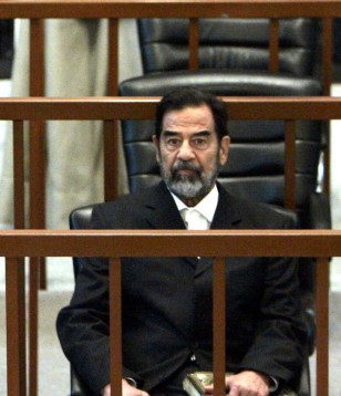 Image: Former Iraqi President Saddam Hussein listens to charges read by Judge Raouf Abdel Rahman during his trial in Baghdad's heavily fortified Green Zone on Monday.