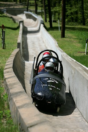 Image: People riding wheeled bobsled.