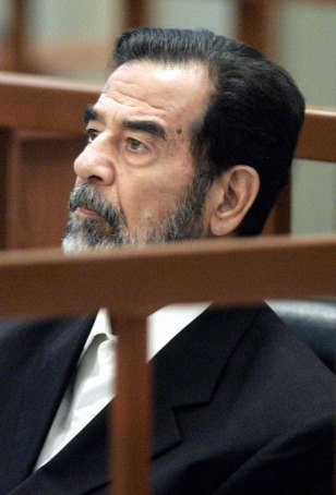 Former Iraqi President Saddam Hussein listens during his trial in Baghdad on Wednesday.