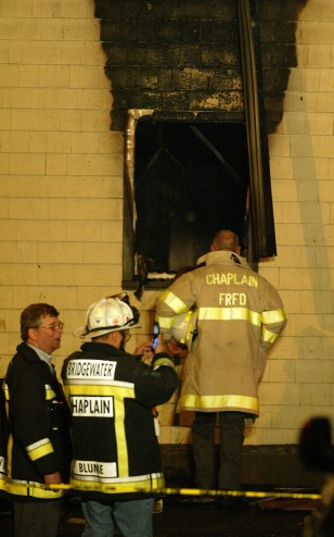 Image: Fire officials examine burned building