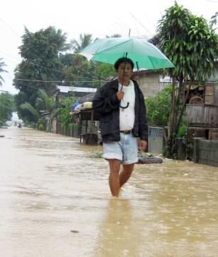 Image: Man walks on flooded street