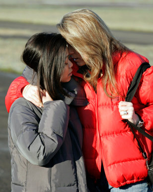 Wives of stranded climbers console each other at the Hood River airport