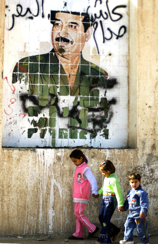 IMAGE: Children pass Saddam poster