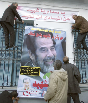 IMAGE: Tunisian workers hang Saddam poster