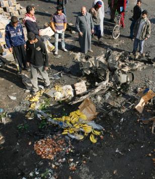 IMAGE: Baghdad residents examine bomb scene