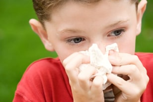 Image: Boy blowing his nose