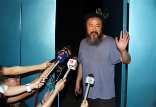 Dissident Chinese artist Ai Weiwei waves from the entrance of his studio after being released on bail in Beijing