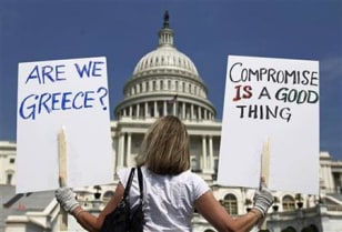 Image: A demonstrator holds placards to protest U.S. debt in front of the Capitol in Washington.