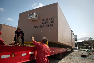 Image: Workers remove modular house used by oil spill relief workers from a marina in Port Fourchon