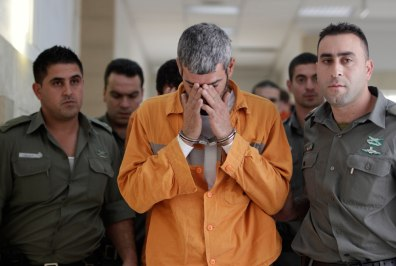 Image: A man charged with murder and attempted killing is escorted by Israeli prison guards in Jerusalem District Court